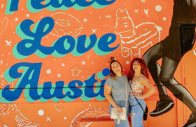 """Caroline and I standing infront of the wall art that says """"Peace, Love, Austin"""" with a girl jumping up."""