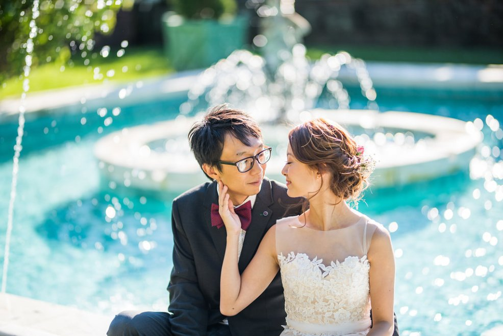 bride and groom sitting by a fountain Kaitlyn Ferris photography garden wedding