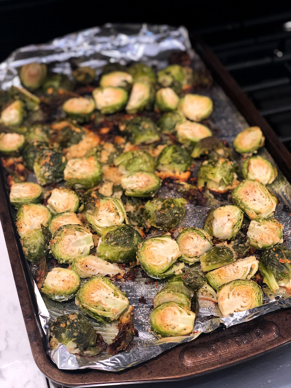 Looking for an easy + delicious recipe for oven roasted parmesan brussels sprouts? This healthy side dish is made with garlic, cheese, healthy oils, + is baked in the oven to give them a nice crispy bite! Save this pin for upcoming family holiday dinners like Thanksgiving + Christmas [because everyone will want seconds!]. Feel free to add bacon, balsamic, honey, maple syrup, or any other flavors you desire with this quick veggie dish. #brussels #sprouts #Christmas #Thanksgiving #roasted