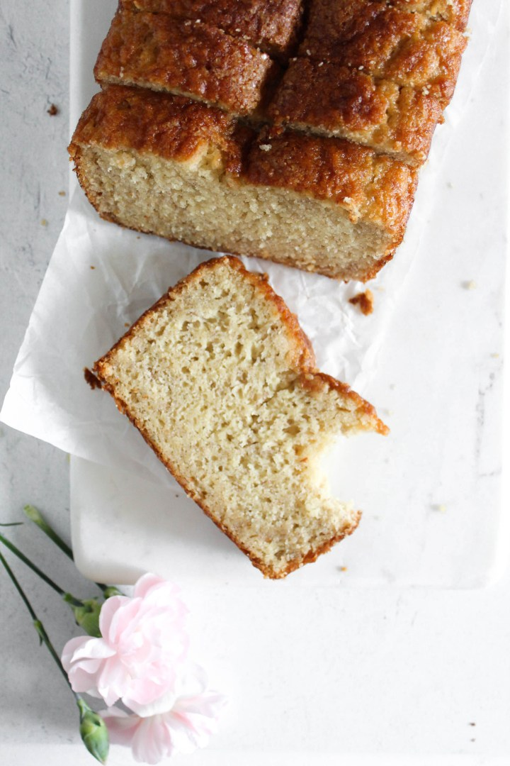 overhead view of slices of bisquick banana bread on parchment paper, a bite is taken out of the banana bread.