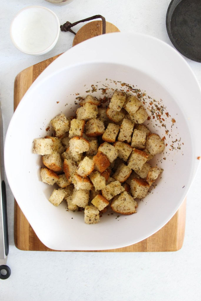 croutons in mixing bowl with seasonings.
