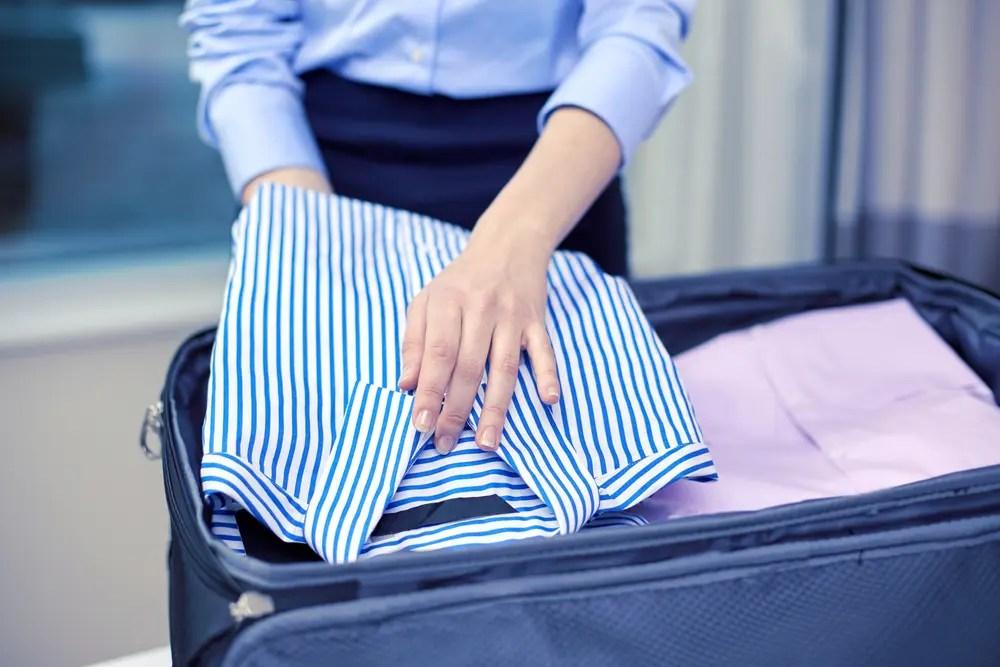 旅行用バッグに洋服をつめている男性