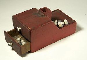 box with draw slots for black and white marbles