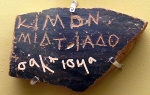 broken black pottery piece with Greek lettering