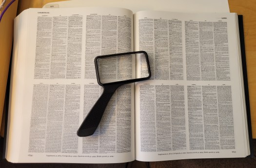 Large open book with magnifying glass