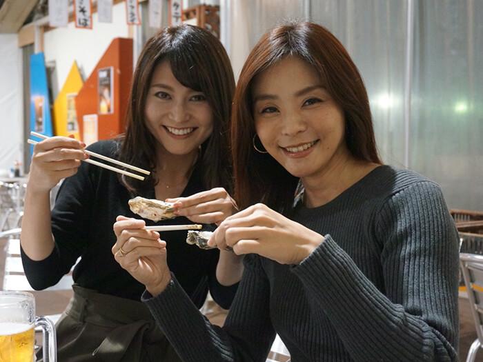 女性2人が牡蠣を食べている風景