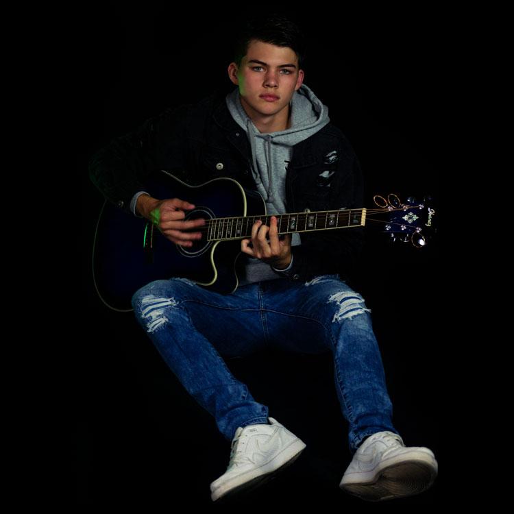 kaleb sitting playing acoustic guitar