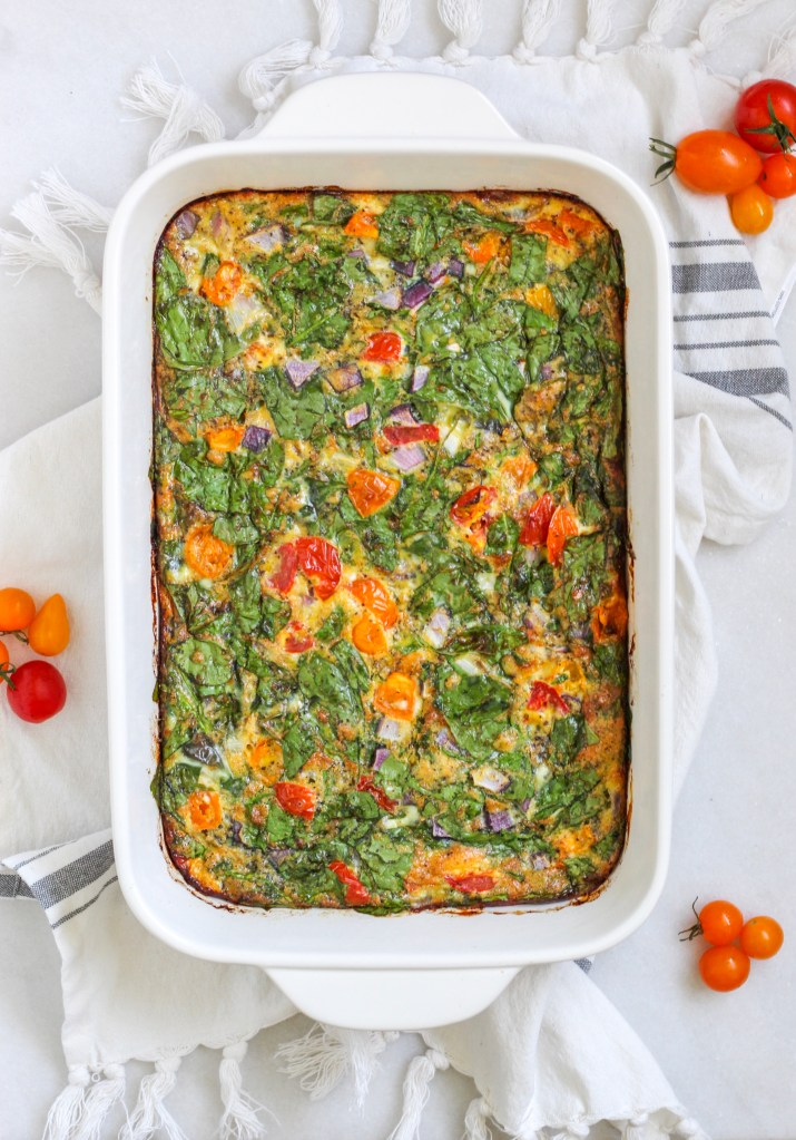 A white casserole dish placed on a towel surrounded by cherry tomatoes and filled with colorful spinach and tomatoes