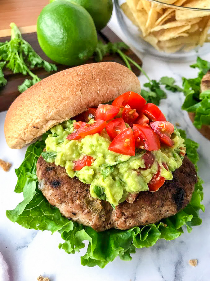 Top angle view of a green chile turkey burger sitting on a lettuce leaf topped with guacamole and tomatoes with tortilla chips and limes in the background