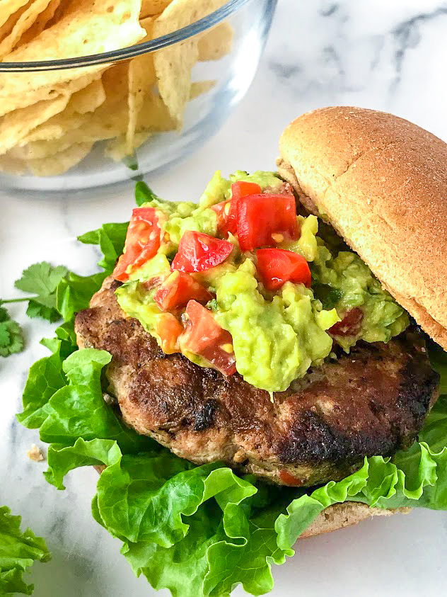 Side view of a green chile turkey burger and guacamole with a whole wheat bun and chips in the background