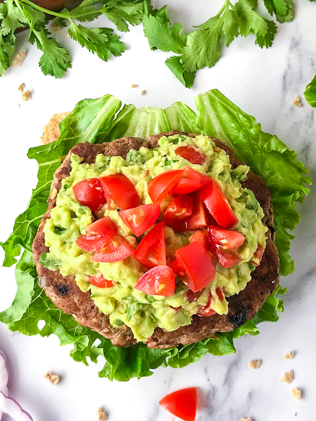 Homemade guacamole with chopped tomatoes sitting on a turkey burger and lettuce