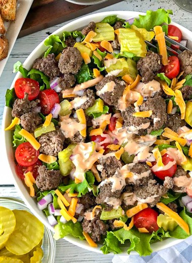 Cheeseburger salad made with ground beef, lettuce, tomatoes, onions, pickles, cheddar cheese and thousand island dressing in a white bowl