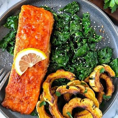 An easy meal featuring baked maple mustard salmon, crispy sauteed kale and roasted delicata squash sitting on a gray dinner plate.