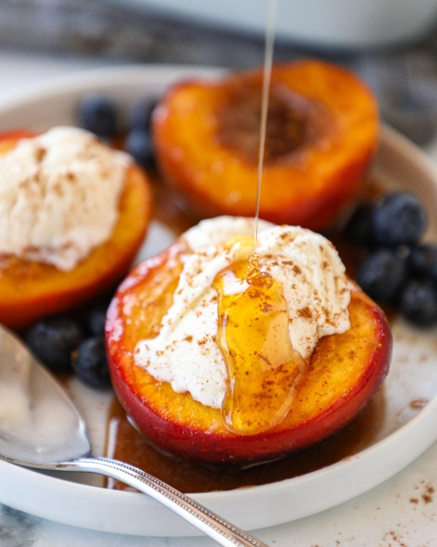 Close up of a baked nectarine half topped with a scoop of vanilla ice cream and drizzled with cinnamon honey sauce