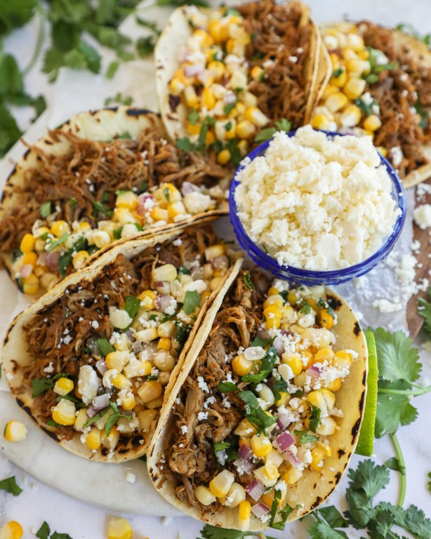 Pork carnitas tacos with Mexican corn salsa sitting on a white marble tray
