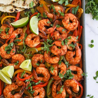 Shrimp fajitas, bell peppers and onions laid out on a sheet pan with tortillas, lime and sour cream