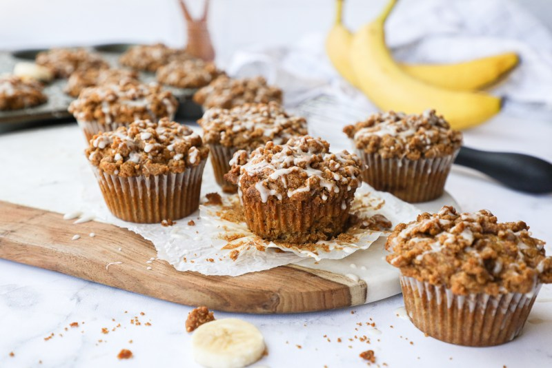 Healthier banana muffins with a sweet crumb topping and drizzled with a vanilla glaze! They're the perfect pastry for any time of the day!