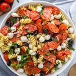Pepperoni pizza pasta salad with mozzarella balls in a large white bowl sitting next to cherry tomatoes and a blue linen napkin
