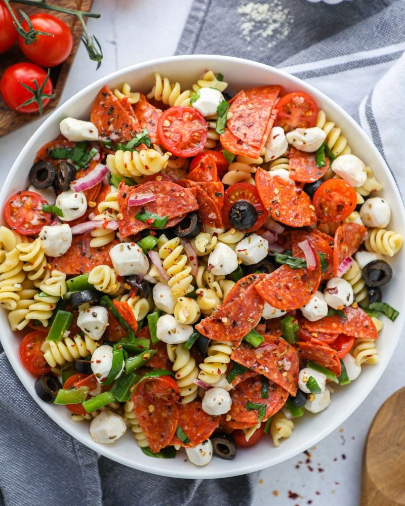 Pizza pasta salad in a white bowl sitting on a blue napkin next to cherry tomatoes