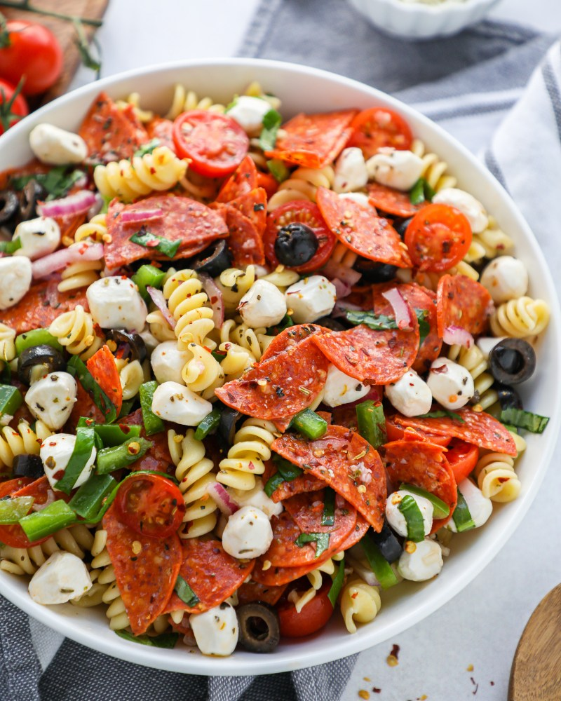 Close up of pizza pasta salad in a white bowl sitting ona blue napkin with red flakes flakes sprinkled beside it