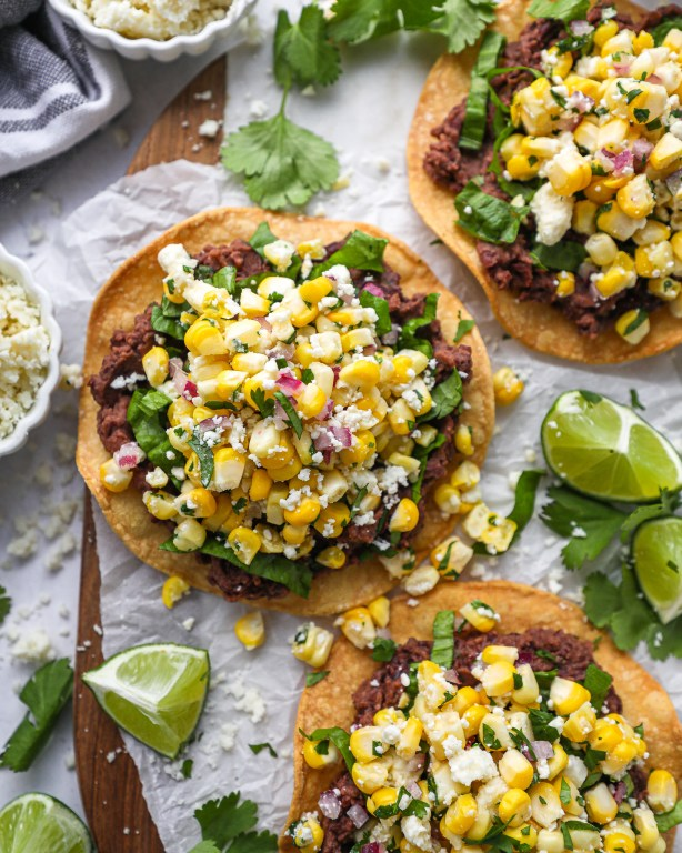 Homemade tostada shells layered with lettuce and Mexican corn salsa sitting on a platter served with lime wedges and cotija cheese