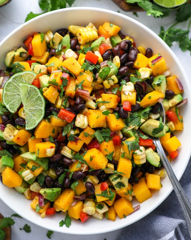 A large white bowl filled with black beans, diced mango, avocado, red onion, red bell pepper, corn and cilantro and tossed in freshly squeezed lime juice