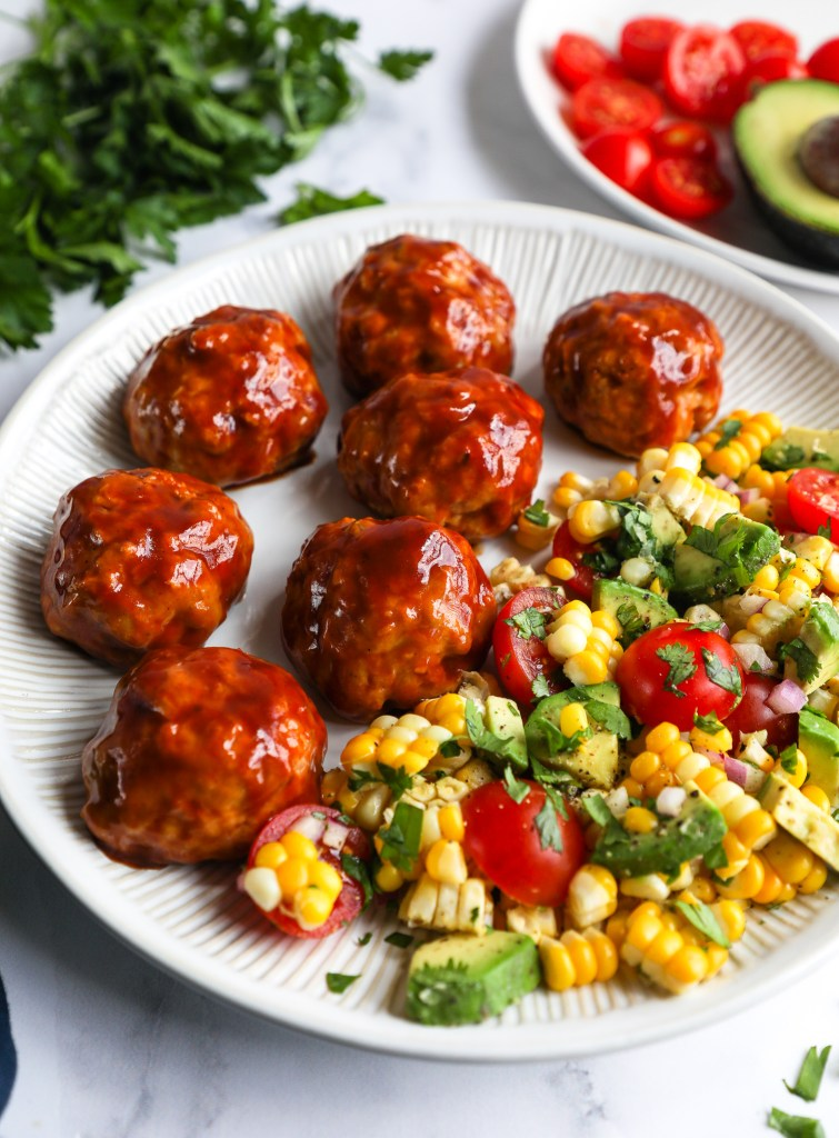 A plate of 7 bbq turkey meatballs covered in bbq sauce sitting next toa plate of corn salad and a bundle of fresh parsley