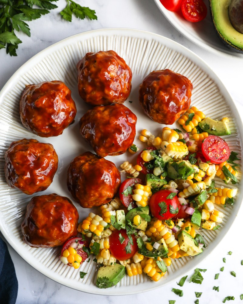 BBQ turkey meatballs sitting on a gray plate served with corn tomato and avocado salad