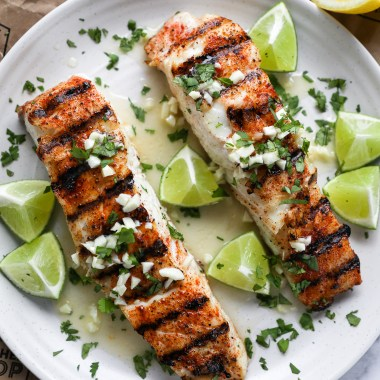 Grilled halibut fillets covered in cilantro garlic lime butter on a white plate surrounded by limes