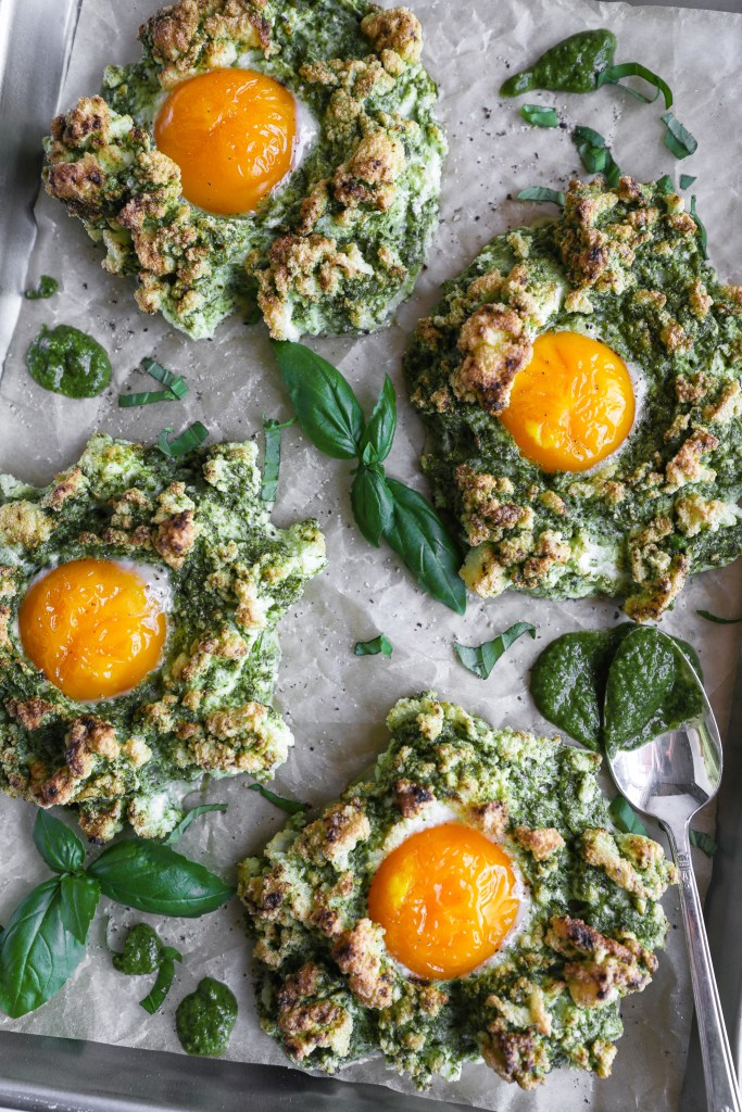4 egg clouds made with pesto sitting on parchment paper with fresh basil pesto drizzled around them