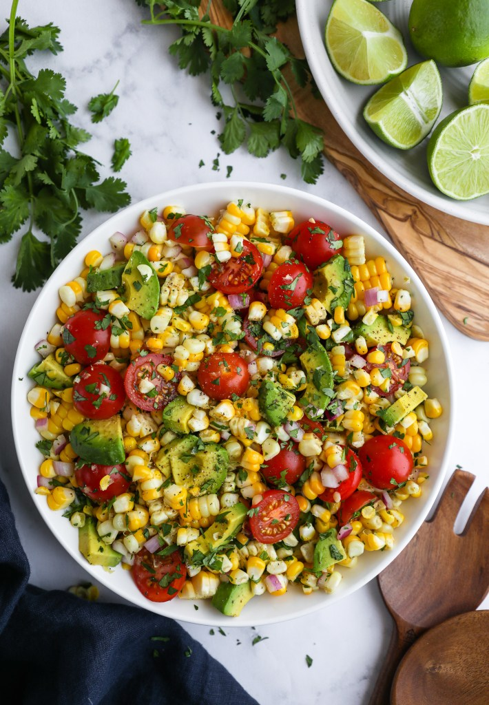 A bowl of summer corn salad with avocado surrounded by wooden salad tongs, lime wedges, bundles of cilantro and a dark blue linen napkin
