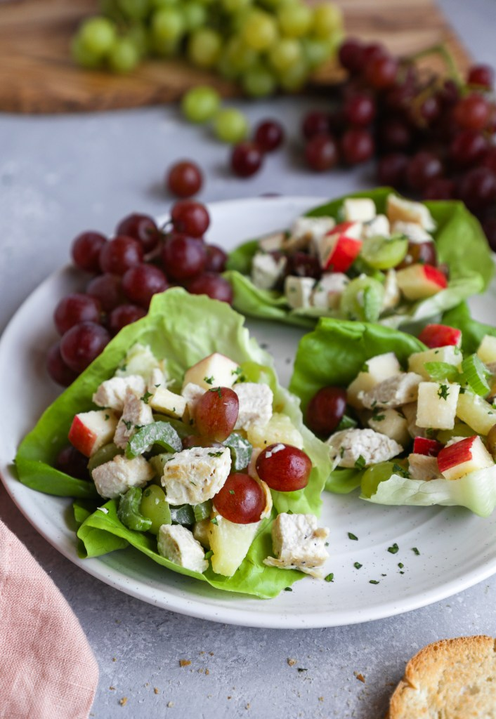 Chicken fruit salad served in lettuce cups  sitting on a white plate next to a vine of red grapes