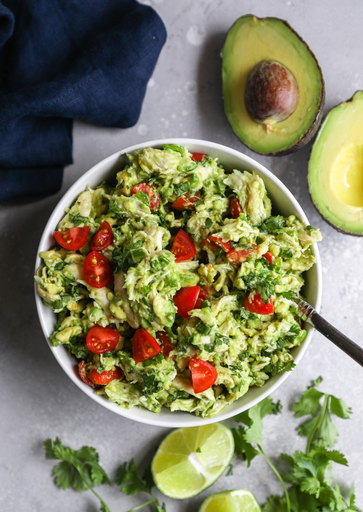 Guacamole chicken salad served in a small bowl surrounded by fresh cilantro, lime wedges and avocado