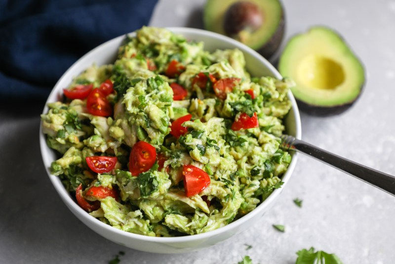 Chicken salad made with fresh guacamole and tomatoes served in a bowl with a silver fork digging into it