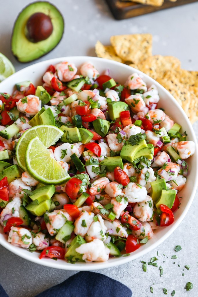 Side angle of a large white bowl filled with shrimp and avocado ceviche sitting next to half of an avocado and lime wedges