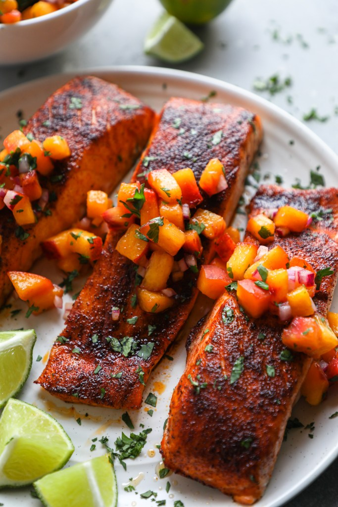 Close up photo of a chipotle salmon fillet topped with a salsa made with peaches, onion, cilantro and lime juice