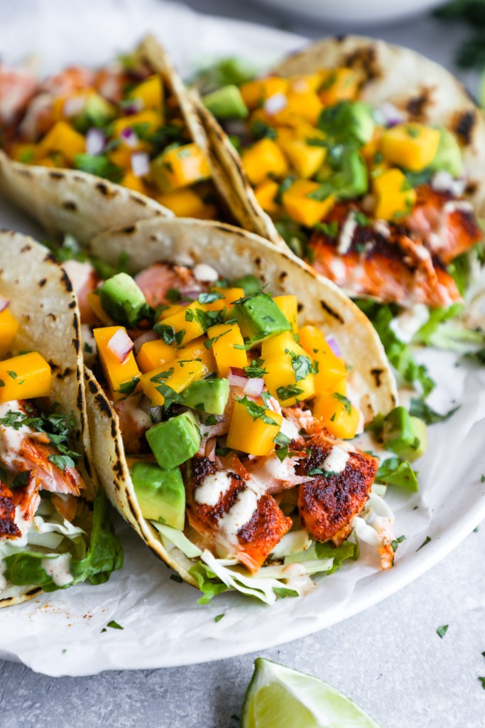 A fish taco made with flakey chipolte rubbed salmon, chipotle lime sauce, cabbage, lettuce and fresh mango salsa
