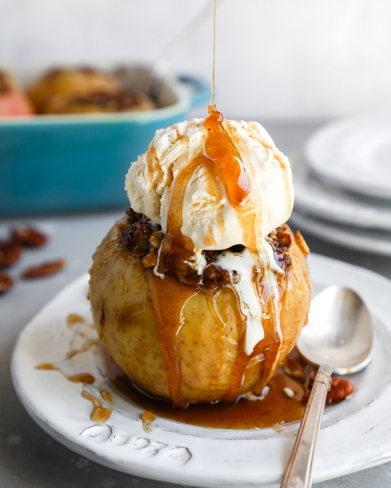 A baked apple topped with a scoop of vanilla ice cream and drizzled with a cinnamon honey sauce