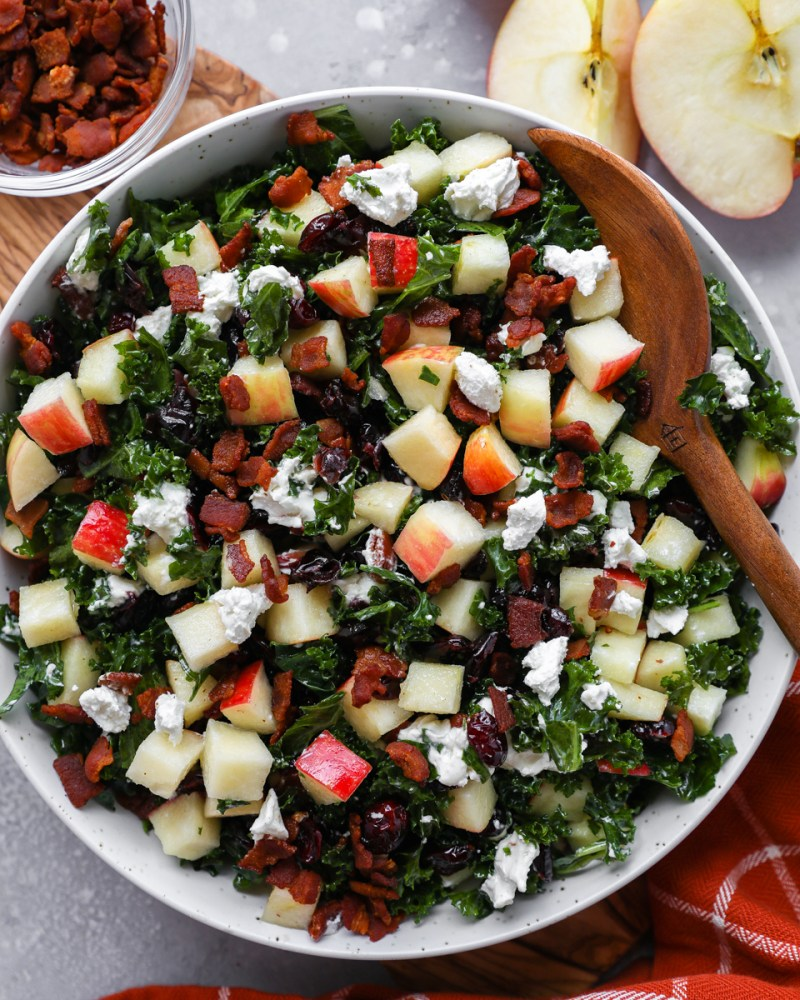 Chopped kale salad with apples, bacon, dried cranberries and goat cheese in a white bowl with a wooden salad tong digging into it