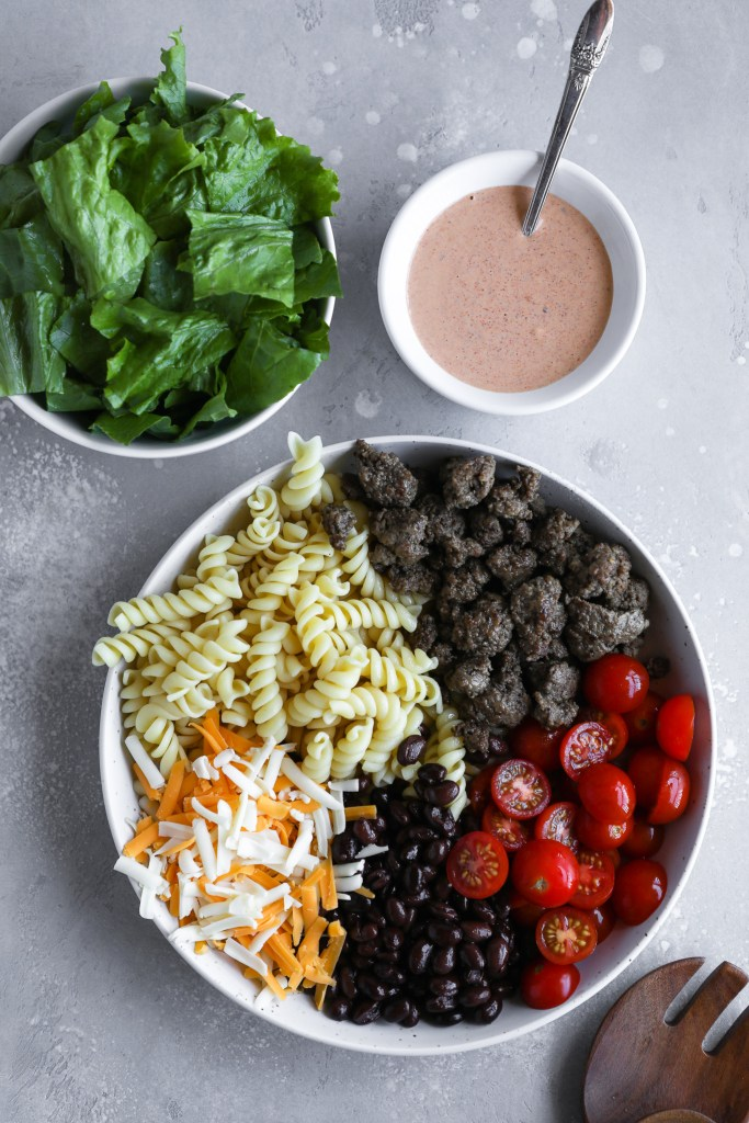 Ingredients to make taco pasta salad sectioned out in a bowl