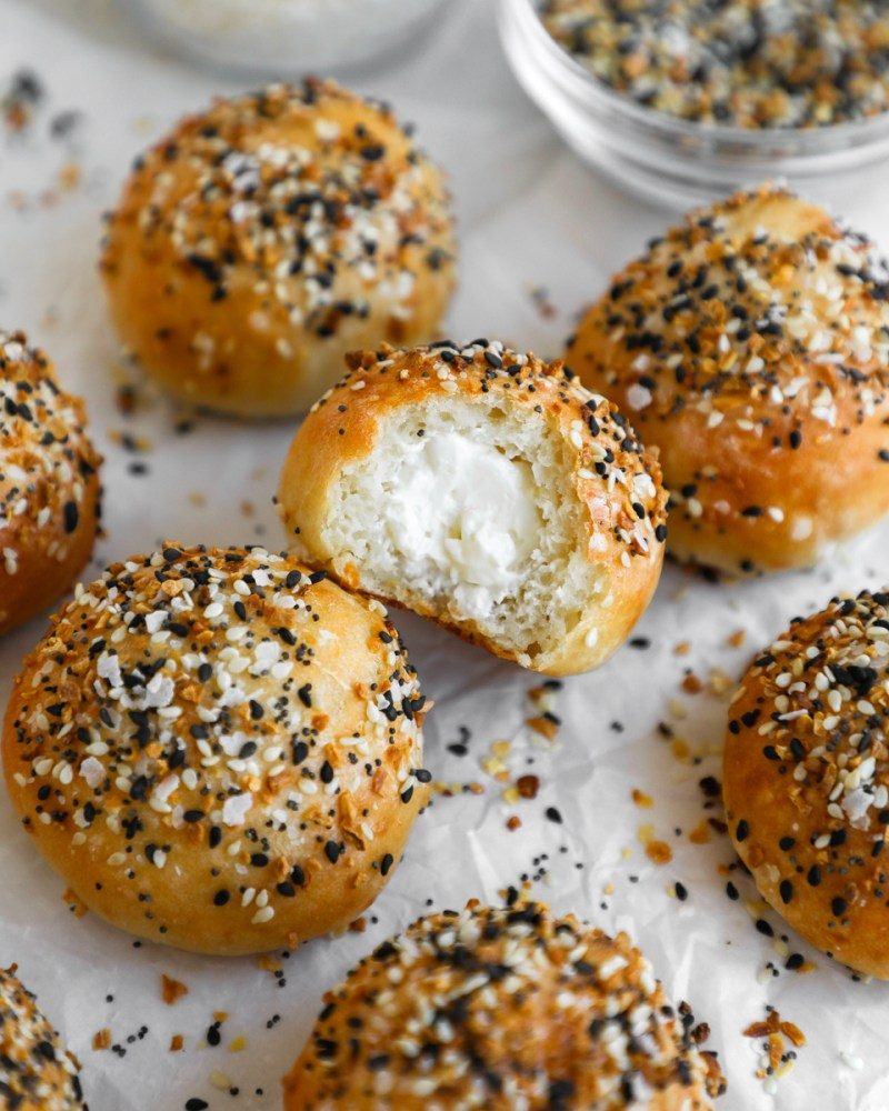 A group of mini everything stuffed bagel bites and one has a bite taken out of it to show the cream cheese filling