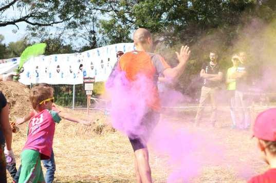 coureur sous une pluie de poudre colorée lancée par un enfant