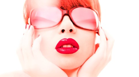 Glamour photo of red haired young woman in red lipstick and red sunglasses