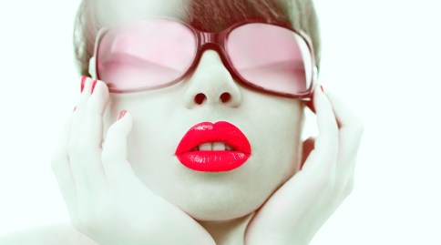 Glamour photo of red lipstick and red sunglasses on young woman