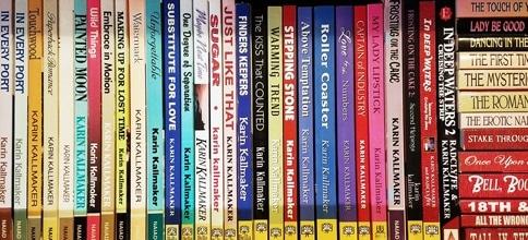 shelf of Karin Kallmaker's books in chron order