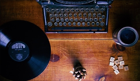 wood desk with typewriter vinyl record scrabble tiles paint and music