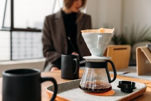 woman works at a desk while coffee brews