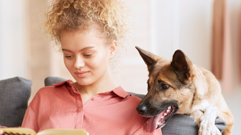 woman reading book with dog looking over her shoulder