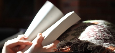 woman reading with cozy blankets
