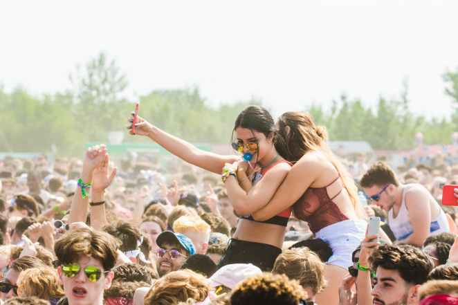 two women embracing surrounded by crowd